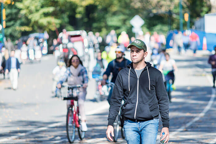 One young serious, thinking man in Midtown Manhattan with people walking on Central Park road in traffic, running, bicycles, bikes on sunny day NYC